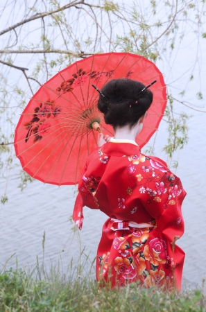 Geisha with red umbrella at the riverside  back view  Stock Photo