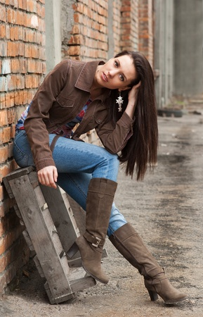 Girl in blue jeans sitting near the brick wall photo