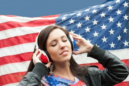 Girl with headphones, USA flag on background photo
