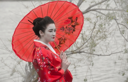 Geisha with red umbrella at the riverside photo