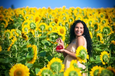 Smiling pregnant woman in sunflowers photo
