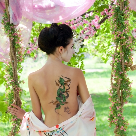 Woman with snake tattoo on her back in the garden Stock Photo