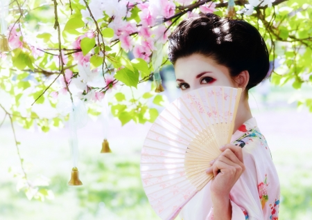 japanese culture: Asian style portrait of young woman with fan in the blooming garden