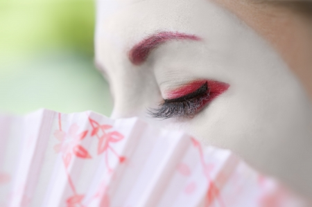 Fragment of a face of young woman with geisha style makeup photo
