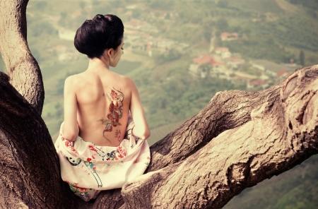 彼女の背中にヘビの入れ墨と木の枝に座っている女性のアジアン スタイルの肖像画