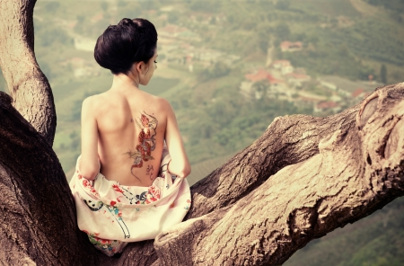 Asian style portrait of woman sitting on the tree branch with snake tattoo on her back  Stock Photo