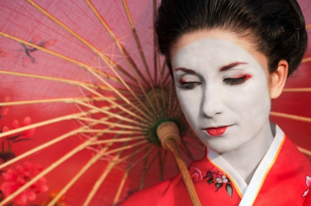 Asian style portrait of young woman with red umbrella photo