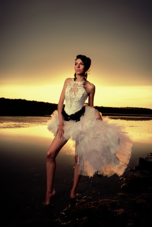 The modern bride standing at the riverside at golden sunset photo