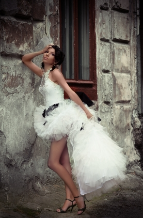 Modern bride leaning against the wall of an old building photo