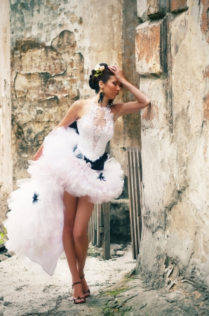 Bride in wedding gown with short skirt leaning against the wall of an old building photo