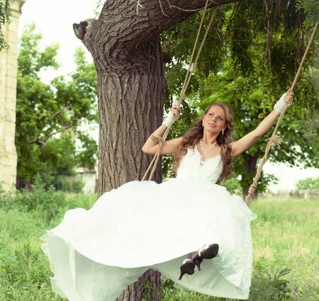 Bride on the swings photo