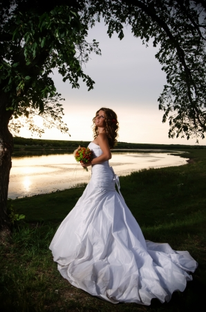 The bride at the riverside under the arch of branches