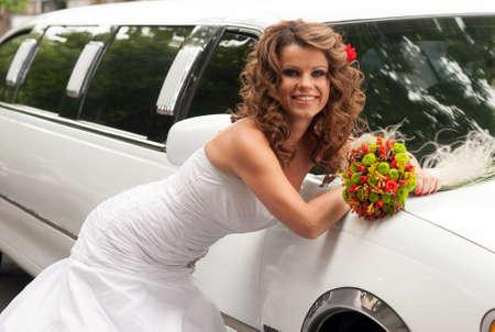 Braut mit Original-Bouquet lehnt auf einem weißen Auto Lizenzfreie Bilder - 14996496