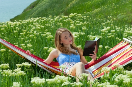 Portrait of woman resting in a hammock and reading a book Stock Photo - 15008034