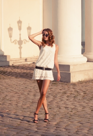 model nice: Pretty woman in short dress standing on the cobblestone road Stock Photo