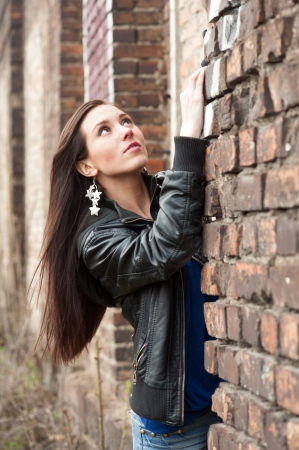 Young pretty girl in black leather jacket near the brick wall photo