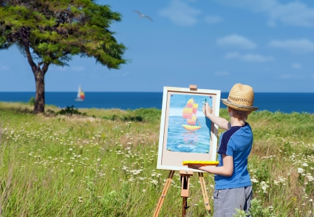artist painting: Young artist finishing his work, outdoor Stock Photo