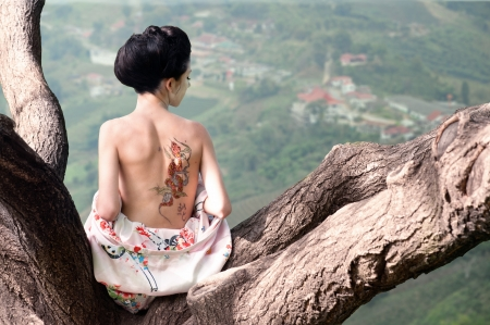 Asian style portrait of young woman sitting on the tree branch with snake tattoo