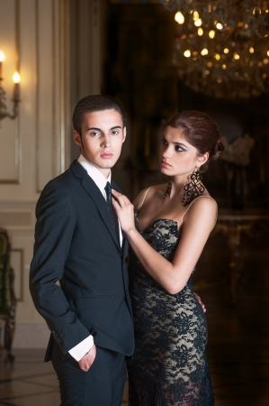 Woman in evening dress and young dark-hair man in suit