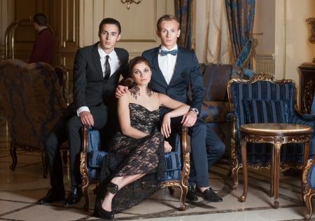 donna ricca: Due uomini e donna in posa in interni di lusso