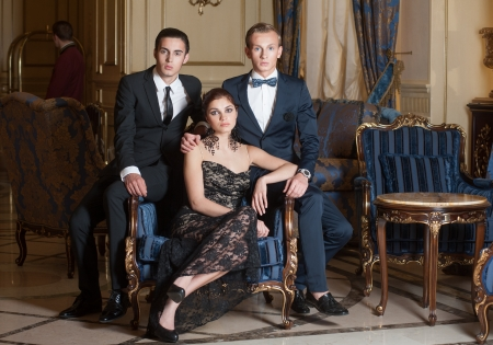 rich people: Two men and woman posing in luxury interior