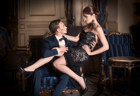Man in suit and woman in evening dress sitting on his lap