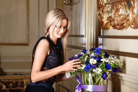 arranging: Pretty blonde woman arranging flowers in a vase in luxury interior