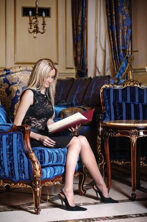Blonde woman reading menu book photo