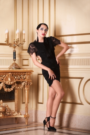 Full-length portrait of retro-style woman in black dress posing in luxury interior  Stock Photo - 15224298