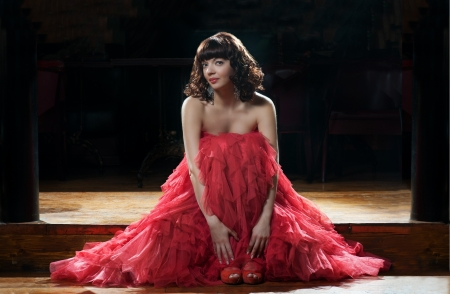 Sitting woman in red evening dress photo