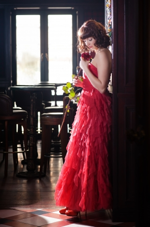 red evening: Woman in red evening dress smelling rose