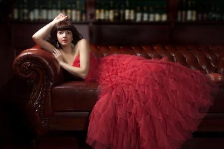 traje de gala: Mujer en vestido de noche rojo tirado en el sofá