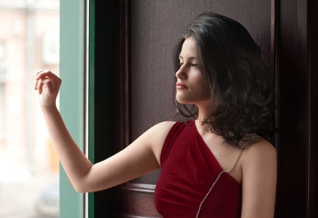 Young woman in red dress looking through window Stock Photo - 15684103