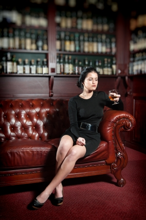 Young woman sitting on the sofa and looking at the glass of brandy in her hand photo