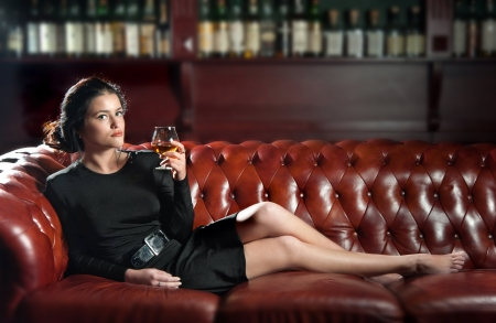 Young woman in black with a glass of brandy lying on the sofa Stock Photo - 15684093