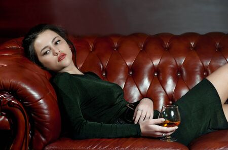 Pensive young woman with a glass of brandy lying on the sofa Stock Photo - 15693777