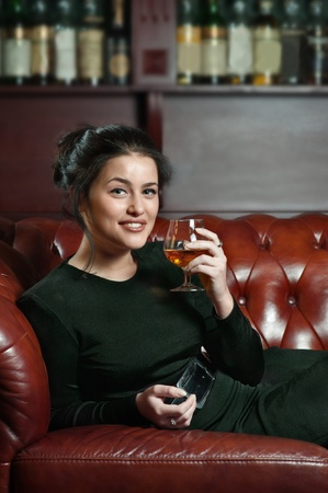 Smiling young woman with a glass of brandy lying on the sofa Stock Photo - 15693778