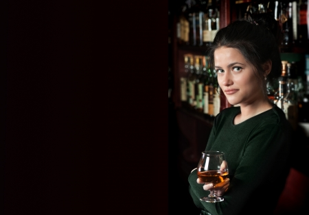 Smiling brunette girl with a glass of brandy against a bar Stock Photo - 15693773