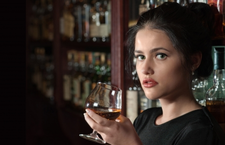 cognac: Brunette girl with a glass of brandy in her hand against a bar Stock Photo