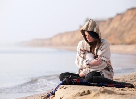 海に対して彼女の猫を持つ少女
