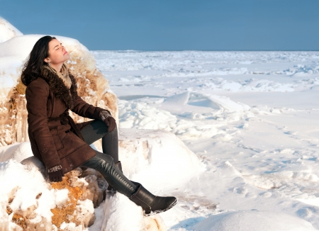 Pretty brunette girl sitting on the rock and basking in the winter sun Stock Photo - 15762509