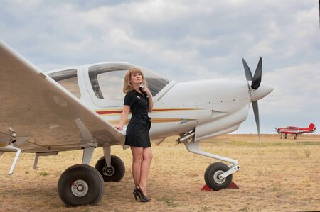 Full length portrait of blond woman leaning on the wing of the little white airplane photo