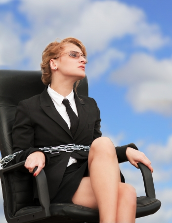 constraint: Out of office - working woman chained to her armchair  blue sky background  Stock Photo