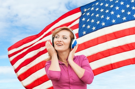 Learning language � American English  blond young woman with headphones, outdoor  photo