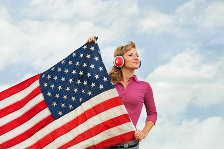 Learning language � American English  blond young woman with american flag, outdoor  photo