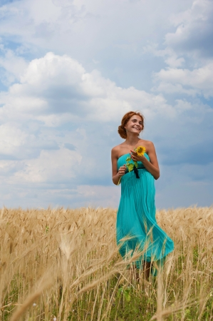 Smiling girl with sunflower in her hands walking through the wheat field photo