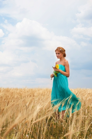 Pretty girl with sunflower in her hands walking through the wheat field photo
