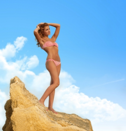 Graceful red-haired woman in bikini standing on the yellow rock photo
