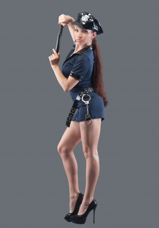 Woman in flirty police uniform, isolated on grey photo