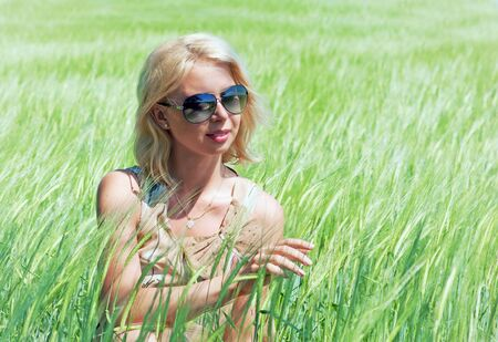 Pretty blond woman touching an ear of wheat in summer field photo